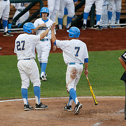 Jun 25, 2013; Omaha, NE, USA; UCLA Bruins third baseman Kevin Kramer (7) is congratulated by first baseman Pat Gallagher (27) for scoring during the third inning in game 2 of the College World Series finals against the Mississippi State Bulldogs at TD Ameritrade Park. Mandatory Credit: Derick E. Hingle-USA TODAY Sports