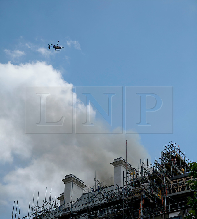 © Licensed to London News Pictures. LONDON, UK  14/06/11. Smoke pours from the roof of a building on fire on Aldwich in London today (Tuesday) as a helicopter hovers overhead. Please see special instructions for usage rates. Photo credit should read Matt Cetti-Roberts/LNP