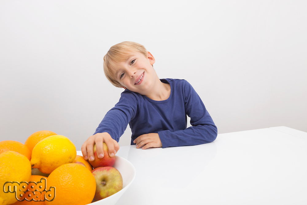 Portrait of boy holding apple from fruit bowl at table