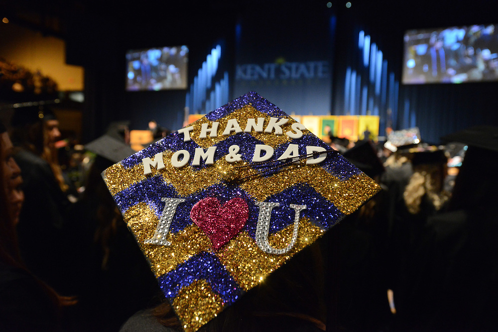 A student sends a message to her parents during the Spring, 2013 commencement ceremonies. Decorating your mortar board with a design or a message is a college tradition.