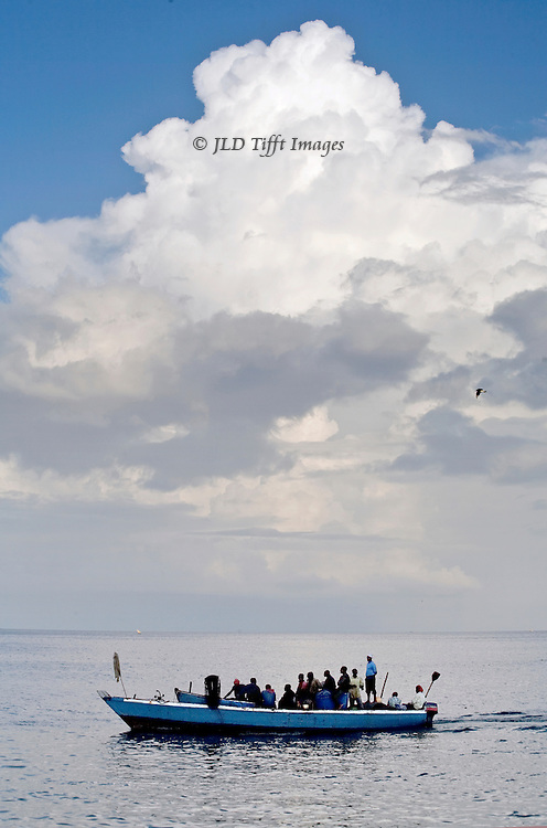 Boatload of fishermen put-put home in a large outboard motor boat, in the dusk, off the coast of Zanzibar.  A mountain of white shining clouds towers over their outboard motor boat, their figures silhouetted against the horizon.