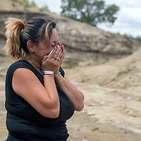 Lisa R. Benally cries at the sight of her mangled car at the base of an arroyo off Zuni Drive In Road in Gallup Wednesday.