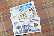 Scottish banknotes from The Royal Bank of Scotland £5, £10 £20 £1 coin on traditional Scottish tartan background
