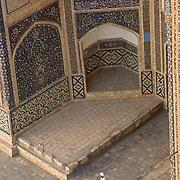 Man standing at entrance to Mir-i Arab Medrassa, Bukhara
