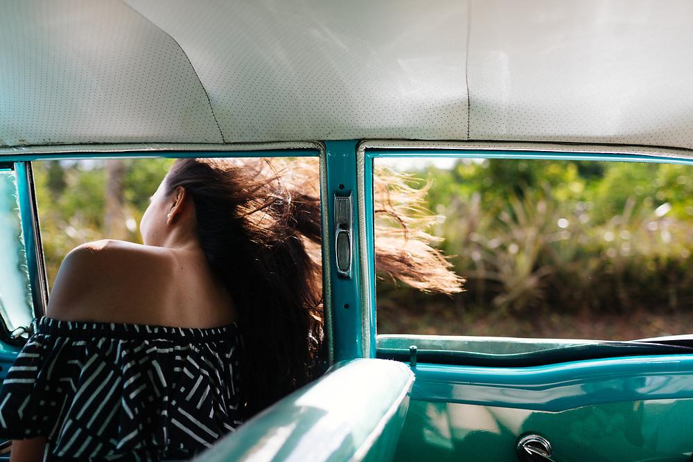 Twenty something laughs in 50's car ride in Vinales, Cuba