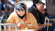 Chloe Kim checks in with social media while her father Jong Kim organizes other elements of the trip in Jack's cafeteria during a mid morning break from the pipe at Copper Mountain, CO. ©Brett Wilhelm/ESPN