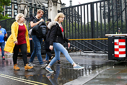 © Licensed to London News Pictures. 24/09/2019. London, UK. A woman jumps over a puddle of rain water gathered at the gates of Houses of Parliament during heavy downpour in London. Photo credit: Dinendra Haria/LNP