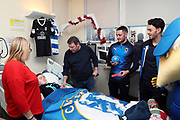 AFC Wimbledon defender Will Nightingale (5), AFC Wimbledon midfielder Anthony Hartigan (8), Haydon the Womble delivering Christmas presents to the children on behalf of AFC Wimbledon, at St George's Hospital, Tooting, United Kingdom on 13 December 2018.