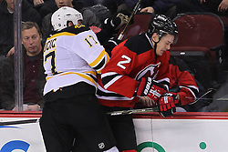 Jan 19; Newark, NJ, USA; Boston Bruins left wing Milan Lucic (17) hits New Jersey Devils defenseman Kurtis Foster (2) during the third period at the Prudential Center.   The Bruins defeated the Devils 4-1.