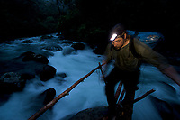 Bird of Paradise researcher Edwin Scholes crosses the river on a pole and vine bridge at dusk after a day in the field observing Birds of Paradise.