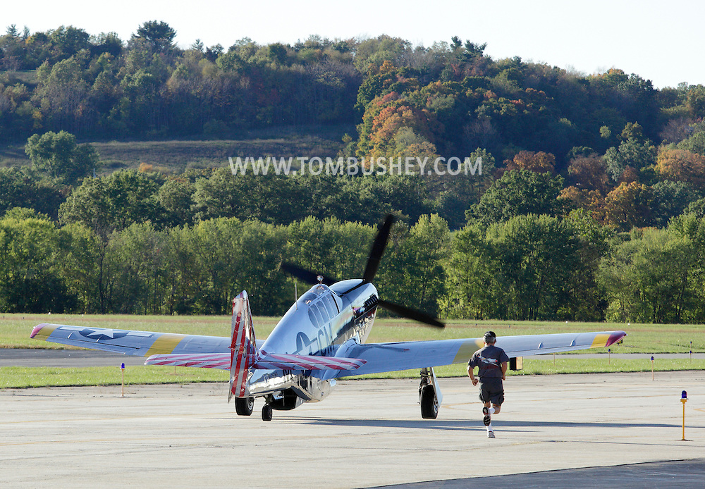 Montgomery, New York -  A crew member runs behind A P-51 Mustang  at Orange County Airport on Oct. 2, 2010.