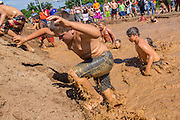 Young children climb out of a muddy watering hole during a race at the 2015 National Red Neck Championships May 2, 2015 in Augusta, Georgia. Hundreds of people joined in a day of country sport and activities.