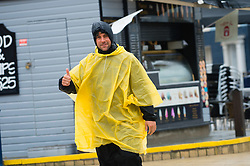 © Licensed to London News Pictures. 2/05/2016. CAberystwyth, Wales, UK.  A man in a bright yellow plastic mac giving the thumbs up as he walks in the rain on the deserted promenade on a dismal,  mild ,wet and grey  Bank Holiday Monday in Aberystwyth Wales. Photo credit: Keith Morris/LNP