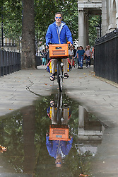 © Licensed to London News Pictures. 09/08/2019. London, UK. A man rides a bicycle in a puddle of water on Whitehall following rainfall in London. Photo credit: Dinendra Haria/LNP
