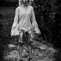 Young blonde female model wearing only a blouse with flared sleeves standing legs apart