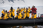 Tourists in zodiac boats watch humpback whales in Wilhelmina Bay, Antarctic Peninsula.