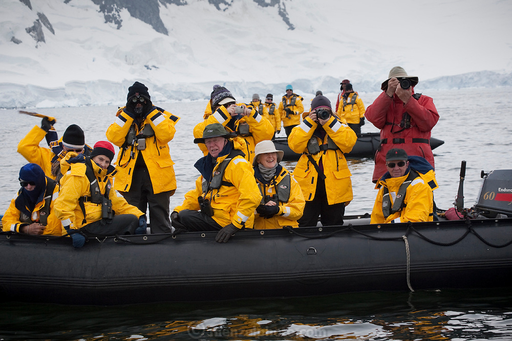 Tourists in zodiac boats watch humpback whales in Wilhelmina Bay, Antarctic Peninsula.