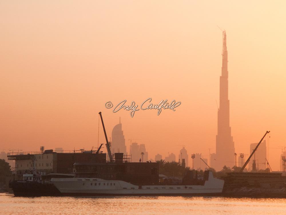 Boats along Dubai creek at sunset with Burj Dubai tower in rear, Dubai UEA