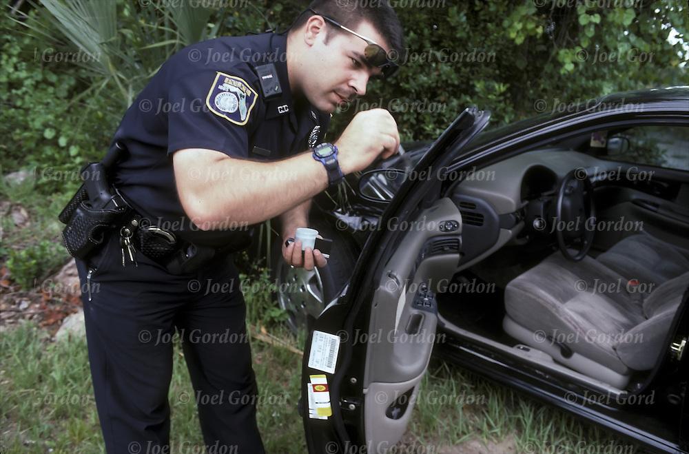 Crescent City Police Officer dusting glass on car door for fingerprints with brush, abandoned stolen car left on dirt road - Putnam County, FL