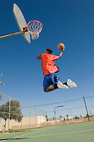 Basketball player mid-air dunking ball side view