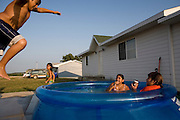 Children keep cool from the summer heat in the newly constructed Heritage Hills housing development in Macy, Nebraska.  From left to right, Christopher Guevara, 11, Ruby Guevara, 4, Alex Guevara, 8, and Sharee Jackson,7...The 203rd Annual Harvest Celebration hosted by the Umonhon (Omaha) Tribe of Nebraska, held at the Wahnashe' Zhinga Park, in Macy, Nebraska from Aug. 2-5, 2007.  .Images taken for The Kellogg Foundation by Kainaz Amaria © 2007.