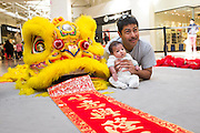 Antonio Chong poses for a portrait with his two-month-old daughter Jia-Li during the Lunar New Year event at the Great Mall of the Bay Area in Milpitas, California, on February 21, 2015. (Stan Olszewski/SOSKIphoto)