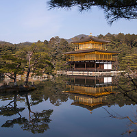 Simply looking upon Kinkaku-ji, the Golden Pavilion, is a lesson in Japanese garden design in which the building works in harmony with its setting. Each level of the building, which was a former villa and is now a Zen temple, represents a different architectural style, Shinden, Bukke, and Zen, with the top two floors covered entirely in gold leaf. Kyoto, Japan.