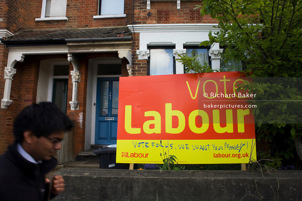 """A male commuter walks past the defaced Labour Party poster which is displayed in a front garden in Herne Hill, South London. The seat of Labour's Tessa Jowell MP, the Minister for the 2012 Olympics. The large sign has had a few extra lines, possibly from a Conservative supporter who has written the words """"Vote for us, we want your money,"""" that means a vote for Labour will take cash from the voter/tax-payer's pocket if Labour are returned to govern the nation. The house is typical of a south London  Victorian terraced home."""