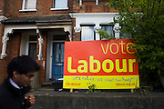 "A male commuter walks past the defaced Labour Party poster which is displayed in a front garden in Herne Hill, South London. The seat of Labour's Tessa Jowell MP, the Minister for the 2012 Olympics. The large sign has had a few extra lines, possibly from a Conservative supporter who has written the words ""Vote for us, we want your money,"" that means a vote for Labour will take cash from the voter/tax-payer's pocket if Labour are returned to govern the nation. The house is typical of a south London  Victorian terraced home."