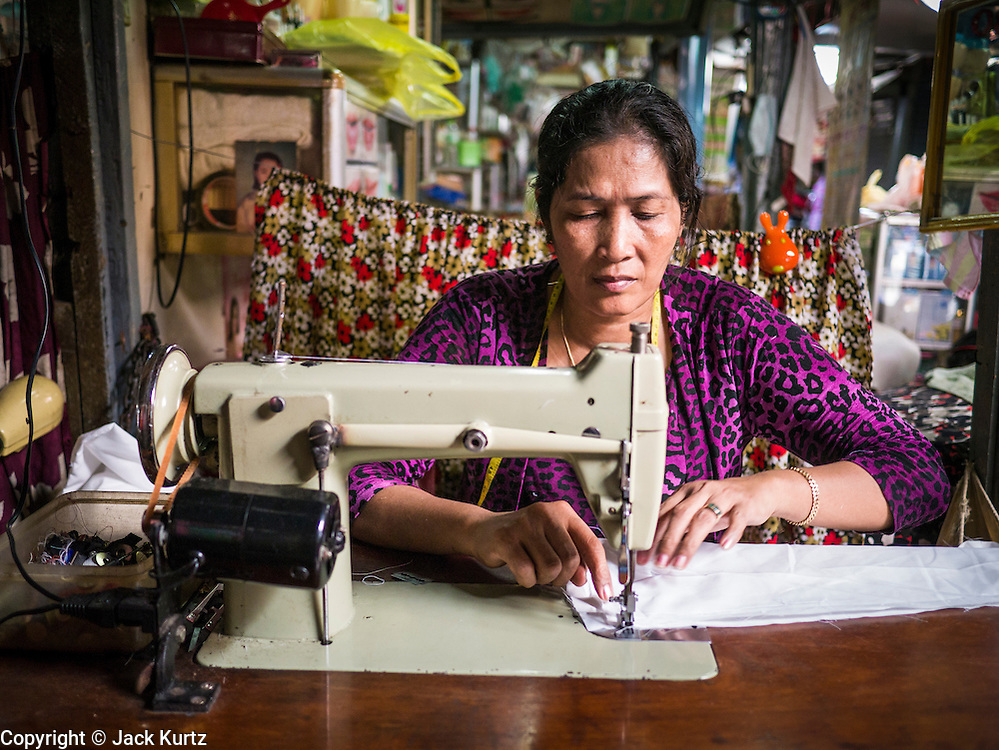02 FEBRUARY 2013 - PHNOM PENH, CAMBODIA:  A seamstress works in a market in Phnom Penh, Cambodia.      PHOTO BY JACK KURTZ