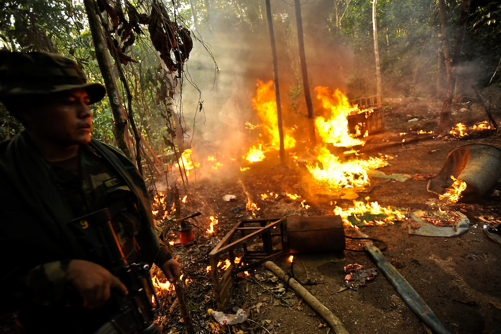 """A cocaine-base processing lab burns after being destroyed by FELCN Special forces in the thick, tropical outskirts of Villa Nuevo Horizonte, a dangerous area in the department of Santa Cruz were narcotraffiking runs rampant. FELCN officials report it is the area of Bolivia most thickly dense of narcotraffickers and cocaine-base processing laboratories.  FELCN police commonly referred to it as a """"narco pueblo""""."""
