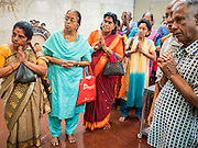 05 JUNE 2015 - KUALA LUMPUR, MALAYSIA:   People pray during the midday prayer in Sri Mahamariamman Temple, the oldest functioning and most important Hindu temple in Malaysia. The principal deity in the temple is Mariamman,  a deity that is popularly worshipped by overseas Indians, especially Tamils, because she is looked upon as their protector during the sojourn to foreign lands. Mariamman is a manifestation of the goddess Parvati, an incarnation embodying Mother Earth with all her terrifying force. She is associated with disease and fever and protects her devotees from unholy or demonic events.    PHOTO BY JACK KURTZ
