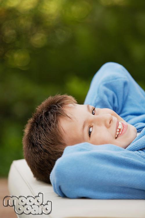 Little Boy Lying Down on cushion in back yard portrait