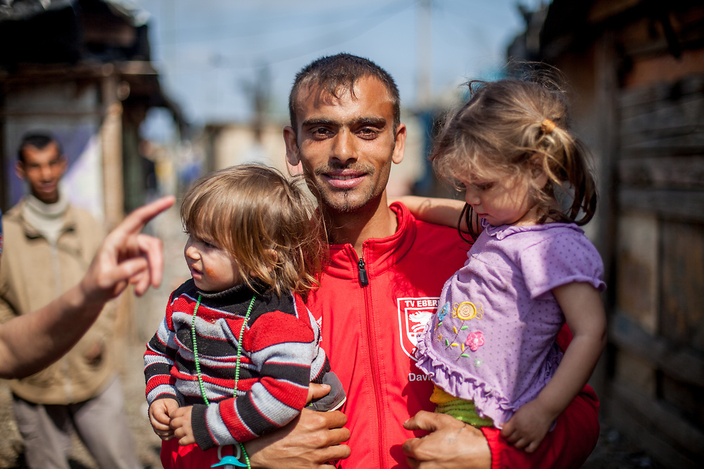 "A young father with his two children at the Roma settlement located at ""Budulovska Street"" in Moldava nad Bodvou about 30 km from Kosice. From about 800 inhabitants of the segregated settlement 'Budulovska Street' (2014) are roughly 392 children up to the age of 16 years."