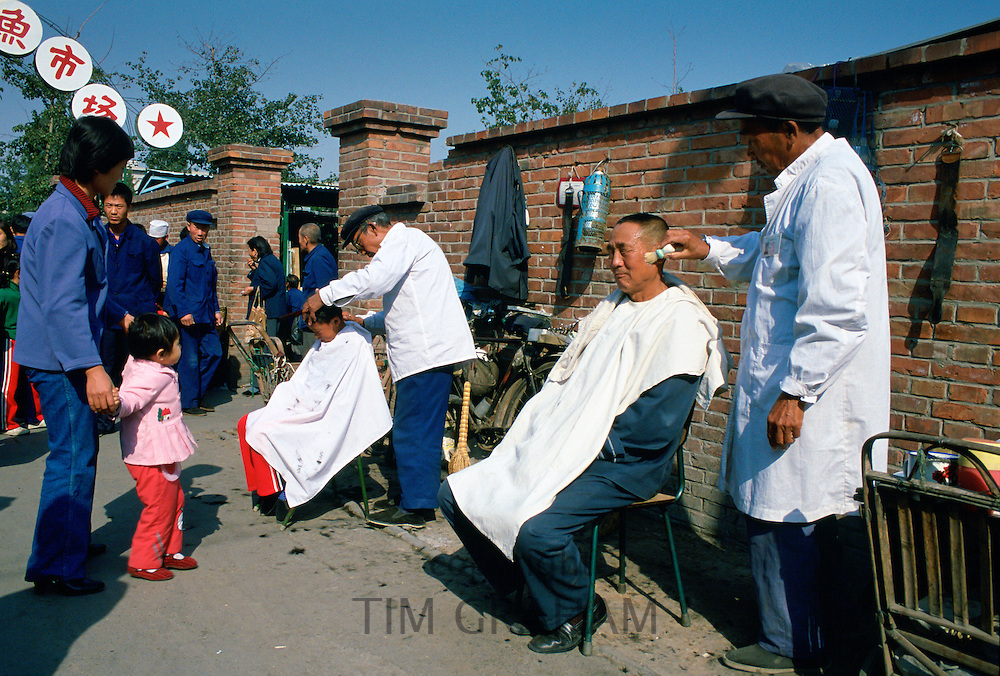 Men at work at an outdoor Barbers' Shop in Old Peking (Beijing), China.  One is using a shaving brush with foam and the other is cutting a young boy's hair watched by a mother and child.