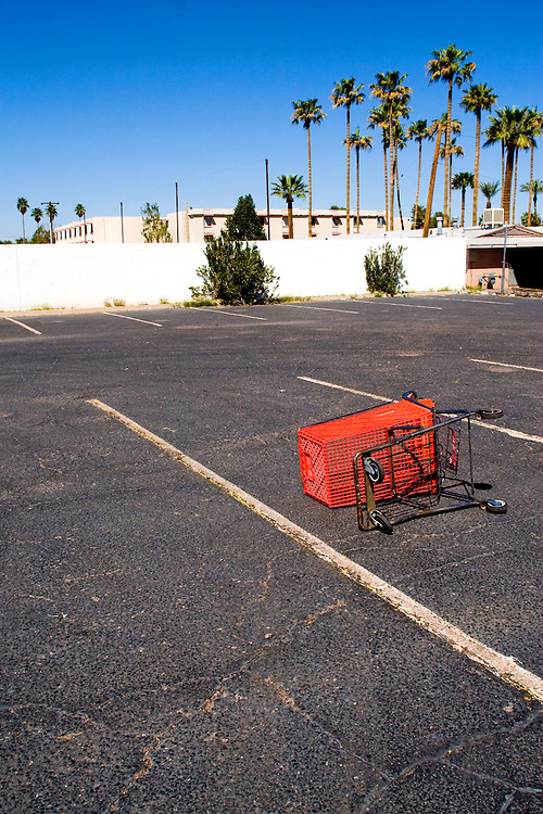 A tipped over shopping cart in an empty parking lot in a warm climate, complete with tall palm trees.