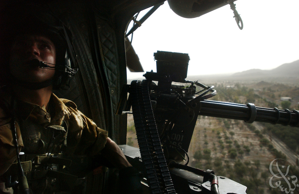 A British Royal Air Force helicopter crewman on patrol watches from the forward gunner position of his Chinook helicopter during a June 18, 2002 mission in southeastern Afghanistan.