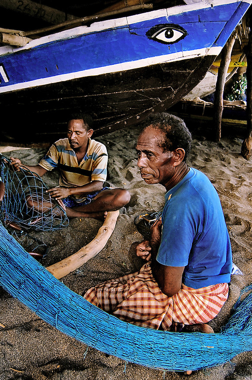 Fishermen mend their nets in a boat shed at Lamalera village on Lembata Island, Indonesia.
