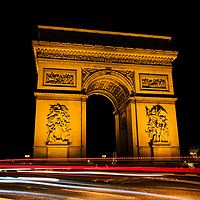 Passing headlights are rendered as streaking lights during a long exposure in front of the Arc de Triomphe, Paris, France, 2013