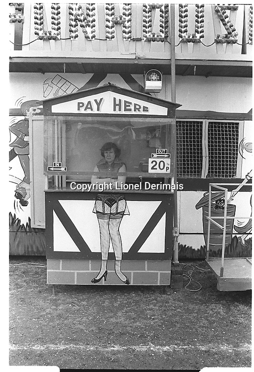 Woman cashier working at a fair, Blackheath, London street photography in 1982. Tri-X