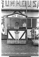 Woman cashier working at a fair, Blackheath, London street photography in 1982. Tri-X