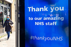 © Licensed to London News Pictures. 27/03/2020. London, UK. A woman wearing a face mask walks past a 'Thank you to our amazing NHS staff' digital display at a bus stop in north London, showing appreciation to the NHS staff. Photo credit: Dinendra Haria/LNP