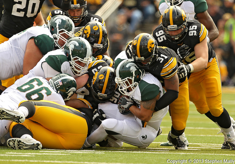 October 6 2013: Michigan State Spartans running back Nick Hill (20) hits a wall of Iowa Hawkeyes defenders during the second half of the NCAA football game between the Michigan State Spartans and the Iowa Hawkeyes at Kinnick Stadium in Iowa City, Iowa on October 6, 2013. Michigan State defeated Iowa 26-14.
