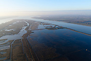"Nederland, Zuid-Holland, Haringvliet, 07-02-2018; oostelijk deel van het eiland Tiengemeten. Het eiland werd oorspronkelijk gebruikt voor de akkerbouw maar is inmiddels 'teruggegeven aan de natuur', de dijken zijn deels doorgestoken, de laatste boer is in 2006 vertrokken. De 'nieuwe natuur' vormt onderdeel van de Ecologische Hoofdstructuur.<br /> The island Tiengemeten in the Haringvliet, was originally used for agriculture but has now ""been given back to nature"". Large parts have been flooded and the isle is part of the National Ecological Network. The last farmer left in 2006. Current use, among other, care farm and camping. <br /> luchtfoto (toeslag op standard tarieven);<br /> aerial photo (additional fee required);<br /> copyright foto/photo Siebe Swart"