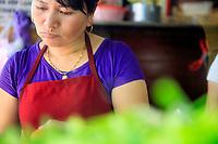 A Vietnamese woman preparing food at the famous restaurant Banh Mi Phuong in Hoi An, Vietnam