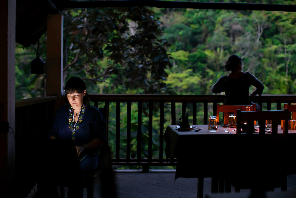 Woman catches up with work in dining area late in the evening, while another takes in sights and sounds of the jungle, in San Ignacio, Belize. Copyright 2014 Reid McNally.