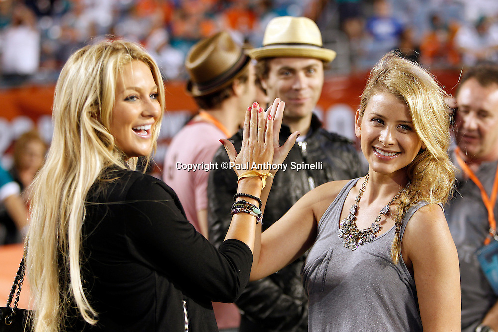 """Cast members of MTV's """"The Hills"""" television show (L-R) Stephanie Pratt and Lo Bosworth smile and high five each other from the sidelines of the Miami Dolphins NFL week 11 football game against the Chicago Bears on Thursday, November 18, 2010 in Miami Gardens, Florida. The Bears won the game 16-0. (©Paul Anthony Spinelli)"""