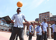 Johannes Tsebe of Knowledge is Virtue Academy in downtown Johannesburg dribbles a ball as his friends look on at Drill hall on 24 October 2009.  Schools in the inner city are not child friendly since the children have to deal with chaotic traffic, noise and limited space. For Johannes and friends however look forward to their break time since they can have a chance to play.