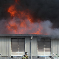 Huge flames burst through the roof as fires continued to spread at American Furniture in Ecru Friday morning.