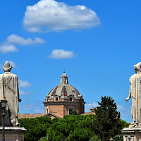 Castor and Pollux Statues with Church of the Ces&ugrave; Dome in Rome, Italy <br /> Dioskouri were mythological twins. Upon the death of Castor (on the right) his brother Pollux asked their father Zeus, the Greek king of all gods, to bring them together again for eternity. The wish was granted by becoming the heavenly constellation of Gemini.  These statues were sculpted around 200 AD. They once stood in the Temple of Castor and Pollux in the Roman Forum. After a significant restoration in 1584, they were placed on either side of the Cordonata ramp which leads to the Capitoline Museums. In between them in this photo is the dome of the Church of the Ces&ugrave;. Built in 1580, it has two distinctions: it is the mother church for the Society of Jesus, commonly called Jesuits, and it is the first building with a Baroque fa&ccedil;ade.